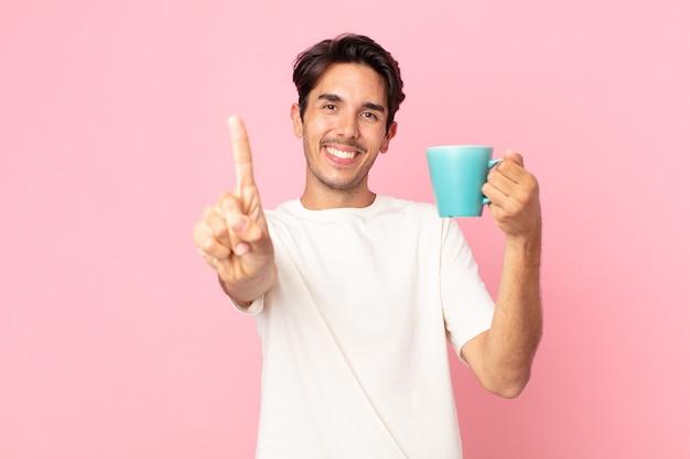 Joven hispano sonriendo con orgullo y confianza haciendo el número uno y sosteniendo una taza de café