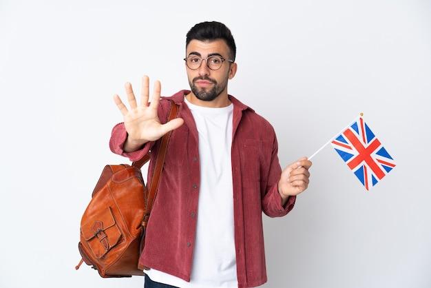 Joven hispano sosteniendo una bandera del reino unido contando cinco con los dedos