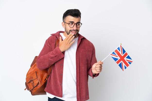 Joven hispano sosteniendo una bandera del reino unido mirando hacia arriba mientras sonríe