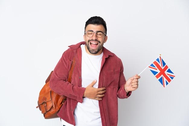 Joven hispano sosteniendo una bandera del reino unido sonriendo mucho