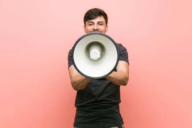 Joven hispano sosteniendo un megáfono gritando emocionado al frente.