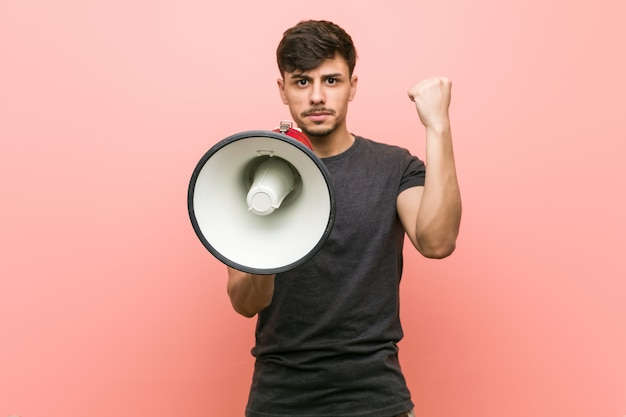 Joven hispano sosteniendo un megáfono mostrando el puño a la cámara, expresión facial agresiva.