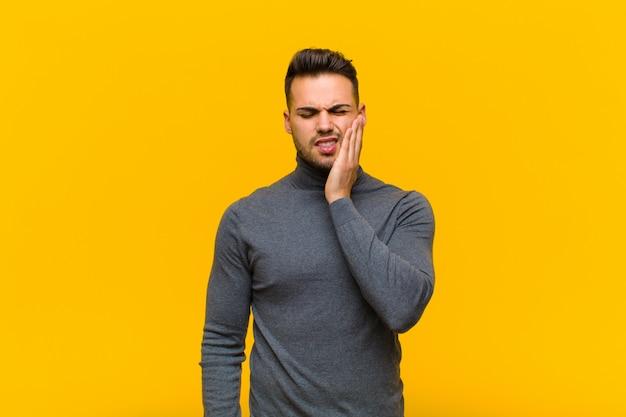 Joven hispano sosteniendo la mejilla y sufriendo dolor de muelas doloroso, sintiéndose enfermo, miserable e infeliz, buscando un dentista contra la pared naranja