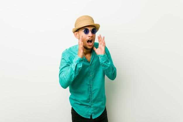 Un joven hispano vestido con ropa de verano grita fuerte, mantiene los ojos abiertos y las manos tensas.