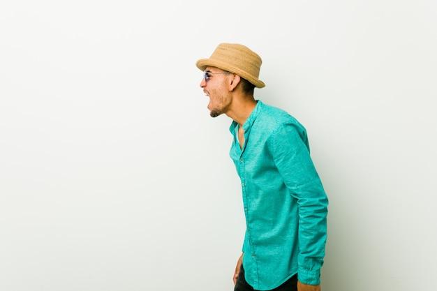 Joven hispano vistiendo una ropa de verano gritando hacia un espacio en blanco