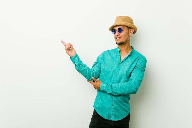 Joven hispano vistiendo una ropa de verano sonriendo alegremente señalando con el dedo de distancia.