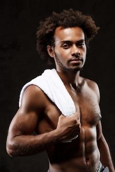 Joven hombre africano deportivo posando sobre pared negra.