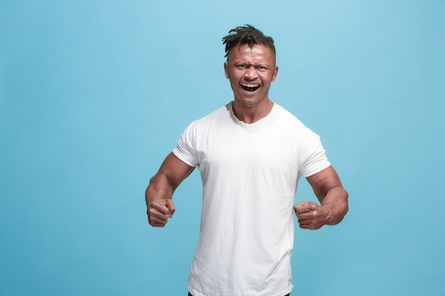 Joven hombre afro enojado emocional gritando en azul