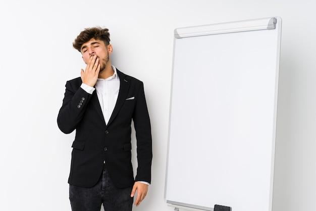 Joven hombre árabe coaching empresarial bostezando mostrando un gesto cansado cubriendo la boca con la mano.