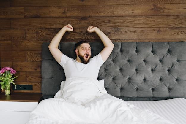 Joven hombre barbudo caucásico bostezando y estirando en su brillante dormitorio moderno en la mañana