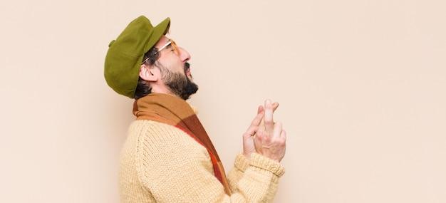Joven hombre barbudo fresco cruzando los dedos con ansiedad y esperando buena suerte con una mirada preocupada