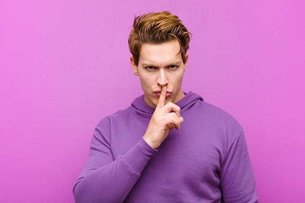 Joven hombre de cabeza roja que parece serio y cruzado con el dedo presionado a los labios exigiendo silencio o silencio, manteniendo un secreto contra la pared púrpura
