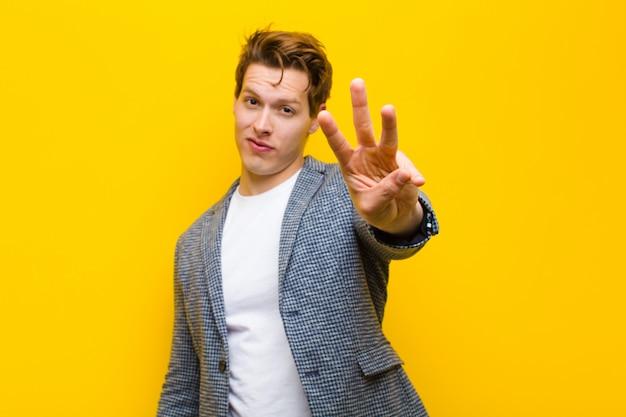 Joven hombre de cabeza roja sonriendo y mirando amigable, mostrando el número tres o tercero con la mano hacia adelante, contando contra el fondo naranja