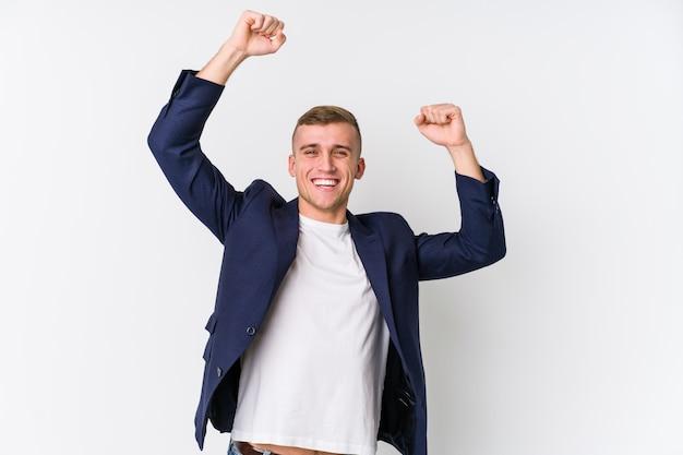 Joven hombre caucásico de negocios celebrando un día especial, salta y levanta los brazos con energía.