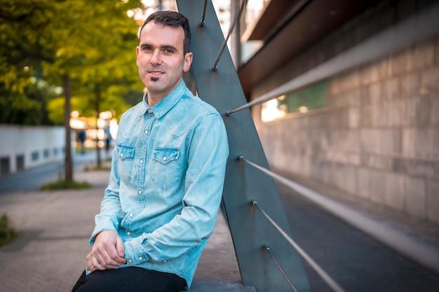 Un joven hombre caucásico de pelo oscuro en una camisa vaquera en la ciudad