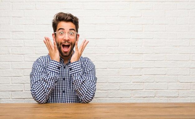 Joven hombre caucásico sentado sorprendido y sorprendido, mirando con los ojos bien abiertos, emocionado por una oferta o por un nuevo trabajo, gana el concepto