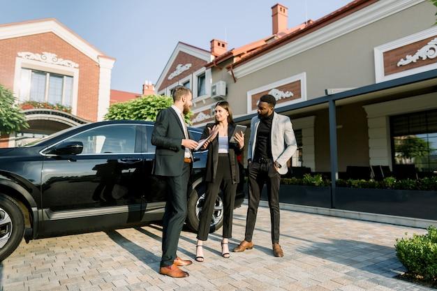 Joven hombre caucásico vendedor de automóviles que trabaja con clientes, pareja de negocios hombre africano y mujer caucásica, en concesionario al aire libre, mostrando crossover de coche nuevo negro