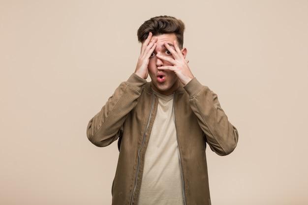 Joven hombre caucásico vestido con una chaqueta marrón parpadeo a través de los dedos asustados y nerviosos.