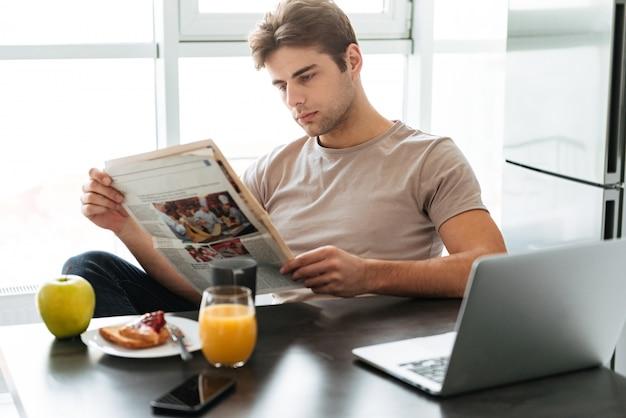 Joven hombre concentrado leyendo el periódico mientras estaba sentado en la cocina