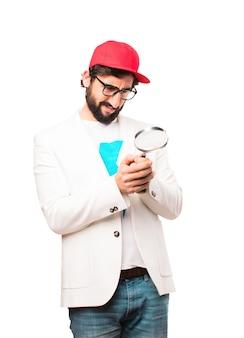 Joven hombre de negocios loco con vidrio magnifyng