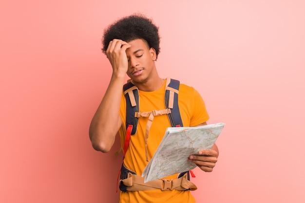Joven hombre explorador afroamericano sosteniendo un mapa preocupado y abrumado