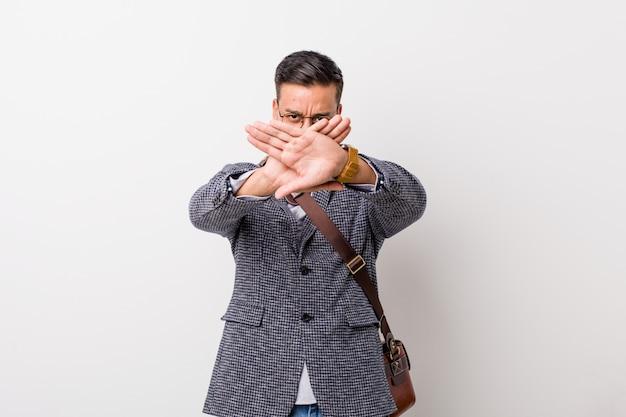 Joven hombre filipino de negocios contra una pared blanca haciendo un gesto de negación