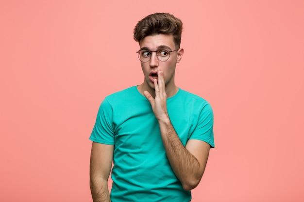 Un joven hombre fresco y caucásico dice una noticia secreta de frenado y mira a un lado