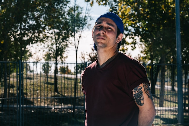 Joven hombre fresco descanso bailarín de pie en el parque. tatuaje en el cuerpo