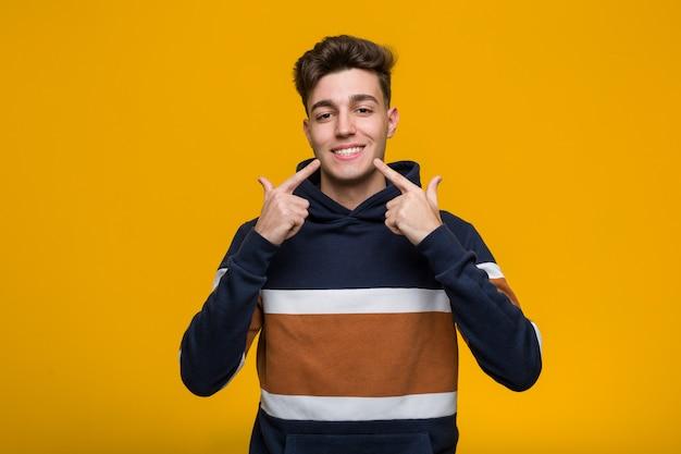 Joven hombre fresco con una sudadera con capucha sonríe, señalando con el dedo a la boca