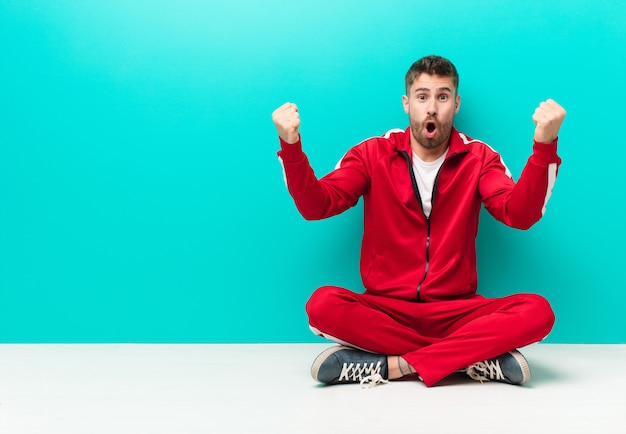 Joven hombre de handosme celebrando un éxito increíble como un ganador, luciendo emocionado y feliz diciendo ¡toma eso! contra la pared de color plano