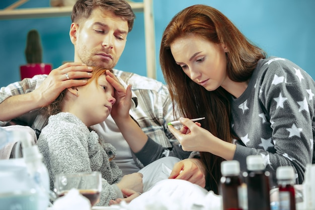 La joven y el hombre con la hija enferma en casa. tratamiento en el hogar. luchando con una enfermedad. asistencia médica. debilidad familiar. el invierno, la gripe, la salud, el dolor, la paternidad, el concepto de relación
