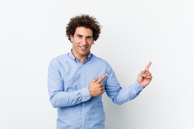 Joven hombre maduro rizado con una elegante camisa apuntando con los dedos a un espacio de copia, expresando emoción y deseo.