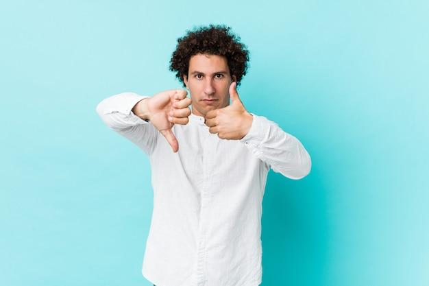 Joven hombre maduro rizado con una elegante camisa mostrando los pulgares hacia arriba y hacia abajo, difícil elegir el concepto