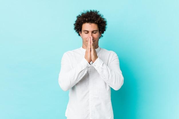 Joven hombre maduro rizado con una elegante camisa tomados de la mano en rezar cerca de la boca, se siente seguro