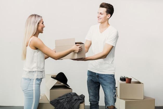 Joven hombre y mujer con caja de cartón