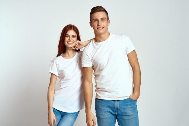 Joven hombre y mujer en camisetas blancas en una luz