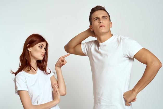 Joven hombre y mujer en camisetas blancas en una pared de luz