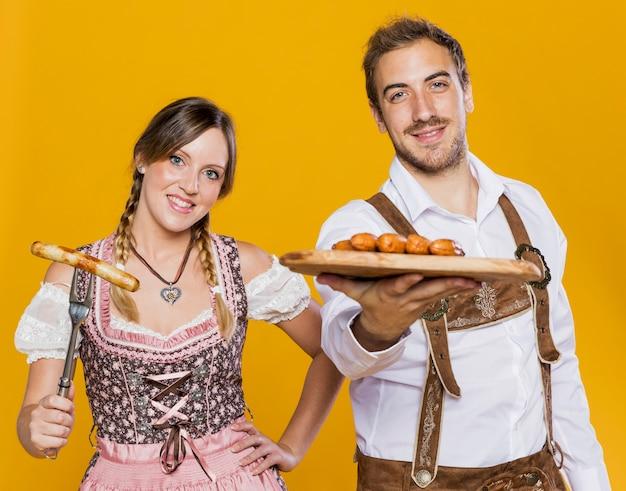 Joven hombre y mujer con comida bávara