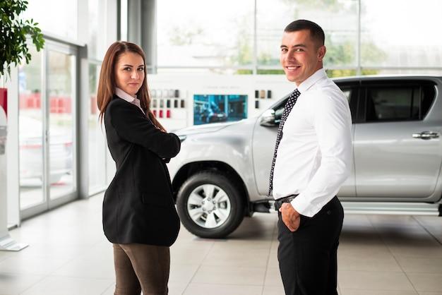 Joven hombre y mujer en concesionario