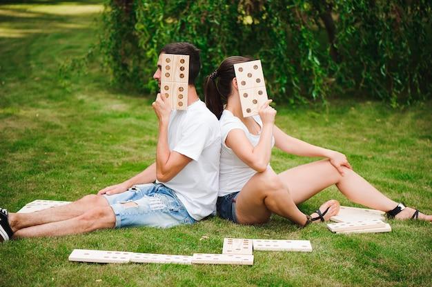 Joven hombre y mujer jugando dominó gigante en el parque en el césped