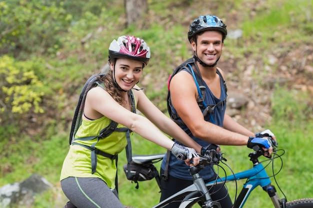 Joven hombre y mujer con moteros en bosque