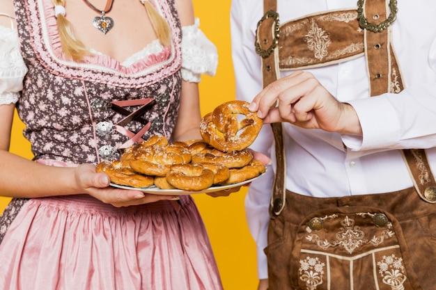 Joven hombre y mujer con pretzels bávaros