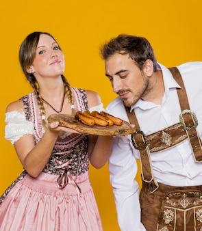 Joven hombre y mujer con salchichas a la parrilla