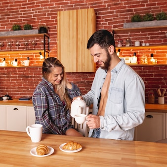Joven hombre y mujer tomando el desayuno con té y cruasanes