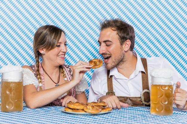 Joven hombre y mujer tratando de pretzels