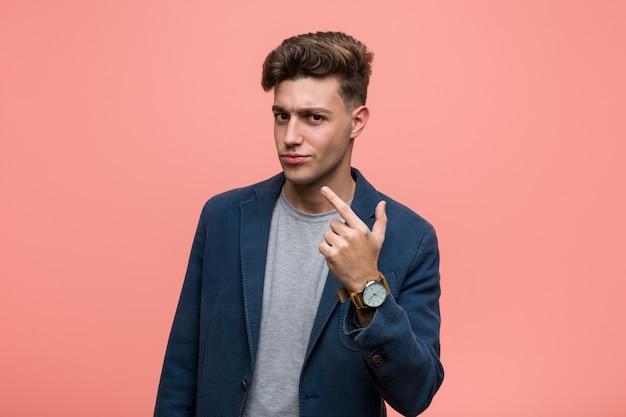 Joven hombre natural de negocios apuntando con el dedo hacia usted como si invitara a acercarse.