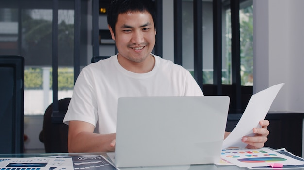 Joven hombre de negocios asiáticos registros de ingresos y gastos en el hogar. hombre preocupado, serio, estresado mientras usa el presupuesto récord de la computadora portátil, impuestos, documentos financieros trabajando en la sala de estar en casa.