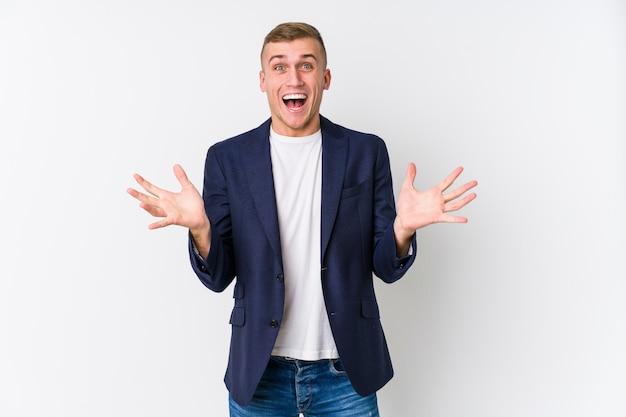 Joven hombre de negocios caucásico celebrando una victoria o éxito, está sorprendido y conmocionado.