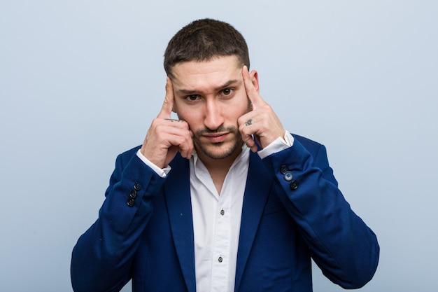 Joven hombre de negocios caucásico se centró en una tarea, manteniéndole los dedos índice apuntando la cabeza.