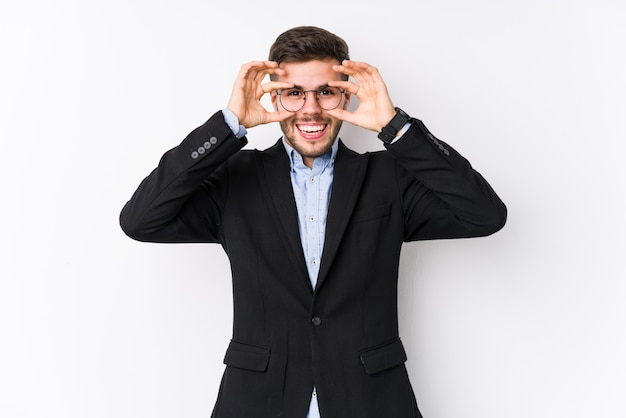 Joven hombre de negocios caucásico posando en una pared blanca aislada joven hombre de negocios caucásico mostrando bien firmar sobre ojos